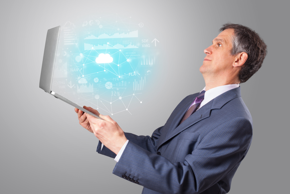 Man holding laptop projecting cloud based system symbols and informations